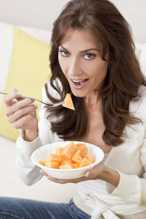 Beautiful smiling brunette woman at home sitting on sofa or settee eating a bowl of fresh cut melon fruit. photo