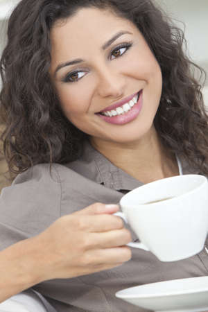 Beautiful young Latina Hispanic woman smiling, relaxing and drinking a cup of coffee or tea Standard-Bild