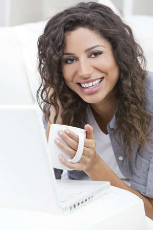 Beautiful young Latina Hispanic woman smiling, relaxing and drinking a cup of coffee or tea using laptop computer photo