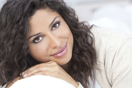 Studio portrait of a beautiful young Latina Hispanic woman smiling resting on her hands photo