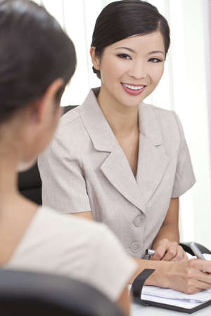 Beautiful young Asian Chinese woman or businesswoman in smart business suit sitting at a desk in an office having a meeting photo