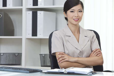 Beautiful young Asian Chinese woman or businesswoman in smart business suit sitting at a desk in an office  photo
