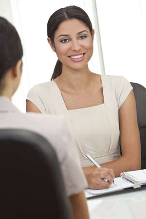Beautiful young Latina Hispanic woman or businesswoman sitting at a desk in an office having a meeting photo