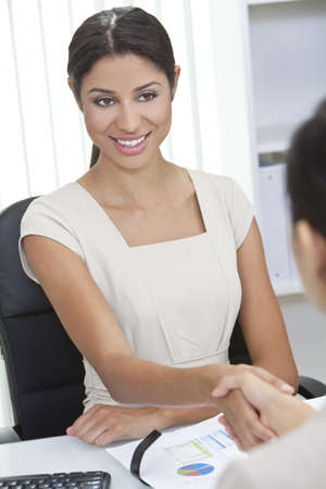 Beautiful young Latina Hispanic woman or businesswoman sitting at a desk in an office meeting shaking hands photo