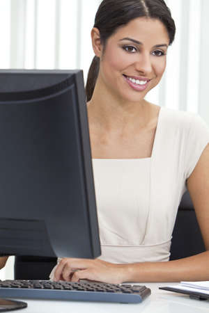 Beautiful young Latina Hispanic woman or businesswoman in smart business suit sitting at a desk in an office using a computer photo