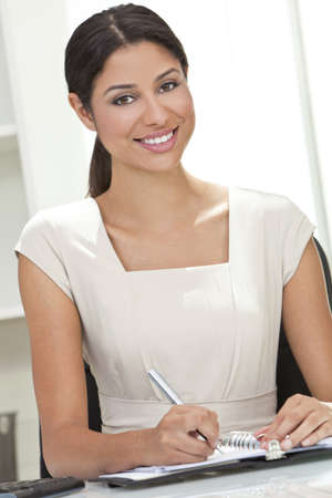 Beautiful young Latina Hispanic woman or businesswoman in smart business suit sitting at a desk in an office writing photo