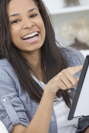 Beautiful happy young African American woman or girl smiling and using a tablet computer at home on her sofa photo