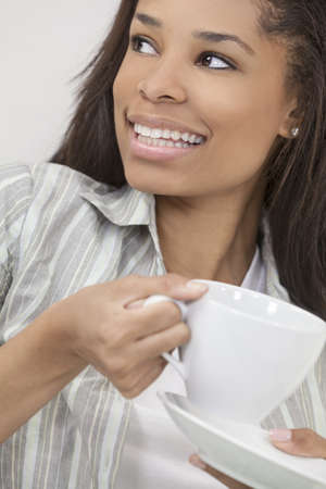 woman drinking tea: Beautiful young African American woman or girl smiling, relaxing and drinking a cup of coffee or tea Stock Photo