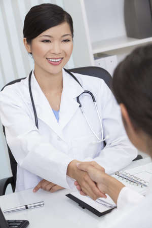 A Chinese Asian female medical doctor shaking hands at a meeting in her hospital office Stock Photo - 14485845