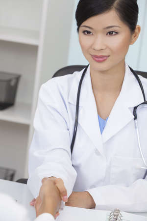 oriental medicine: A Chinese Asian female medical doctor shaking hands at a meeting in her hospital office Stock Photo