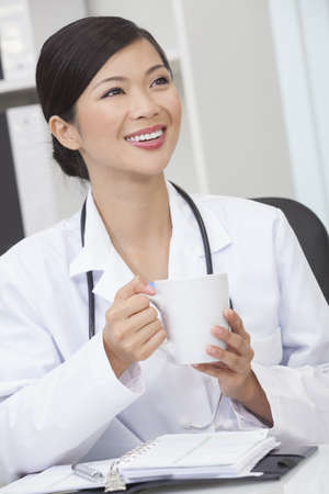 A Chinese Asian female medical doctor drinking tea or coffee in a hospital office photo