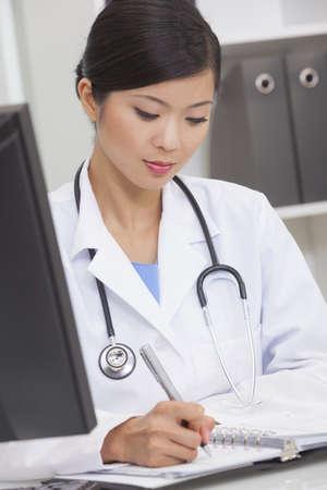 bata de laboratorio: Un chino de Asia doctora médica por escrito en una oficina del hospital Foto de archivo