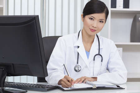 A Chinese Asian female medical doctor writing in a hospital office photo