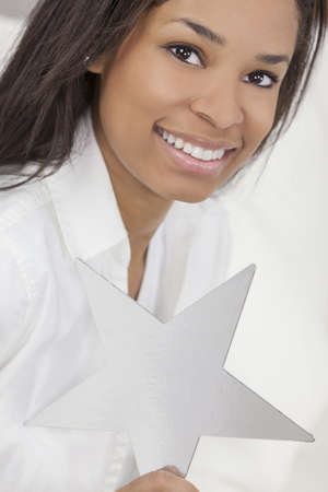 stardom: Portrait of a beautiful young African American woman smiling, relaxing and holding a silver star
