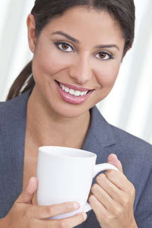 Beautiful young Latina Hispanic woman or business woman smiling, relaxing and drinking a cup of tea or coffee