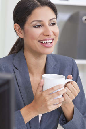 Beautiful young Latina Hispanic woman or business woman smiling, relaxing and drinking a cup of tea or coffee in her office photo