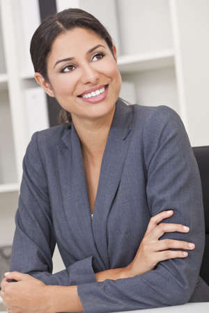 Beautiful young Latina Hispanic woman or business woman smiling and relaxing in her office photo