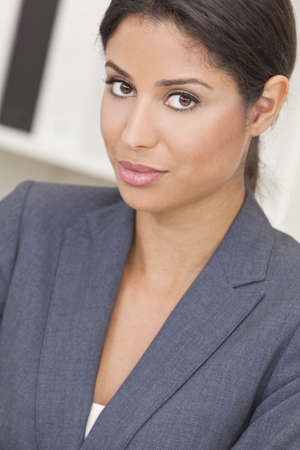latina: Beautiful young Latina Hispanic woman or businesswoman in smart business suit sitting at a desk in an office