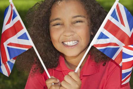 bandera inglesa: Retrato de una joven y bella sonrisa feliz celebración niña de raza mixta interracial ondeando banderas British Union Jack, disparó fuera en el sol de verano