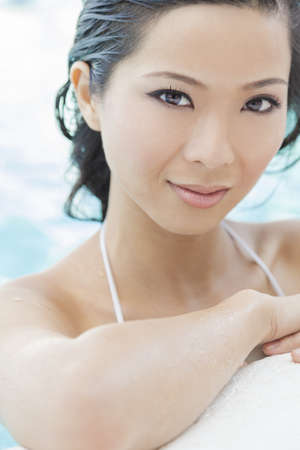 A beautiful sexy young Chinese Asian Oriental woman wearing a bikini and relaxing on the side of a swimming pool  photo