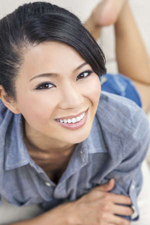 A beautiful young Chinese Asian Oriental woman with a wonderful toothy smile Stock Photo - 14788740