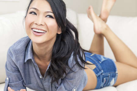 women in jeans: A beautiful sexy young Chinese Asian Oriental woman with a wonderful toothy smile relaxing on a sofa in denim jeans shorts