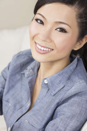 A beautiful young Chinese Asian Oriental woman with a wonderful toothy smile  Stock Photo - 14788732