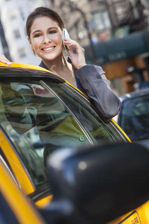 A happy young woman talking on her mobile cell phone by a yellow taxi cab. Shot on location in New York City photo