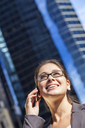 Outdoor portrait of a beautiful young brunette woman or businesswoman talking on her cell phone in a modern city Stock Photo - 14788745