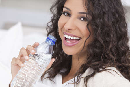 settee: Beautiful young Latina Hispanic woman smiling, relaxing and drinking a bottle of water at home on a sofa Stock Photo