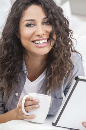 Beautiful young Latina Hispanic woman smiling, relaxing and drinking a cup of coffee or tea using tablet computer photo