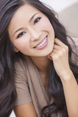 A beautiful young Chinese Asian Oriental woman with a wonderful toothy smile  Stock Photo - 14919060
