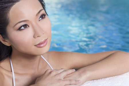 A beautiful sexy young Chinese Asian Oriental woman wearing a bikini and relaxing on the side of a swimming pool. Stock Photo - 14919090