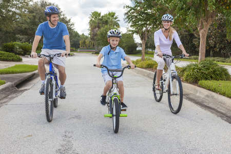 A young family of man and woman parents and one boy child, cycling together. Stock Photo - 14901959