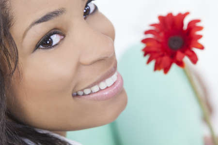 Beautiful happy young African American woman or girl smiling and holding a red gerbera daisy flower Stock Photo - 14936025
