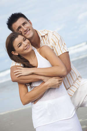 A young man and woman having fun dancing as a romantic couple on a beach with a bright blue sky Stock Photo - 14975689