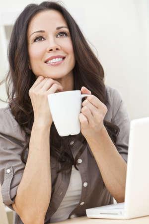 enigmatic: Una bella giovane donna o ragazza con un meraviglioso sorriso enigmatico utilizzo di computer portatile o pc bevendo t� o caff� da una tazza bianca in casa Archivio Fotografico