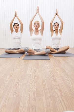 Un grupo interracial de tres mujeres j�venes hermosas que se sienta con las piernas cruzadas en posici�n de yoga en un gimnasio