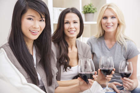 Interracial group of three beautiful young women friends at home drinking red wine together Stock Photo - 14996015