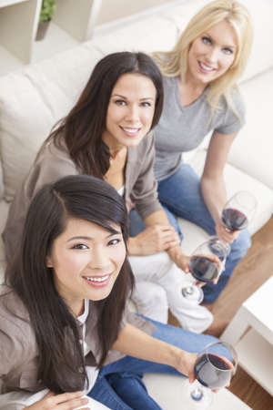 Interracial group of three beautiful young women friends at home drinking red wine together Stock Photo - 14975686