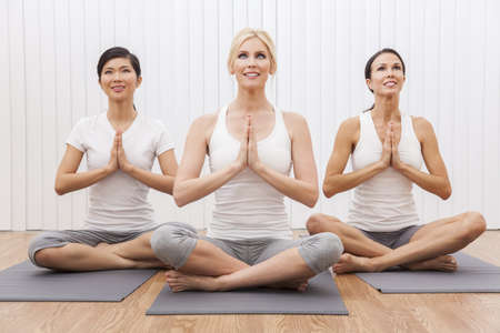 An interracial group of three beautiful young women sitting cross legged in a yoga position at a gym photo