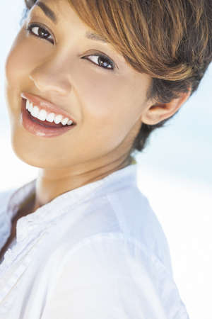 perfect teeth: A beautiful mixed race young woman with perfect teeth laughing shot on a tropical beach Stock Photo