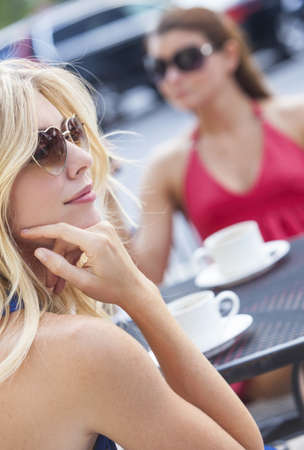 Two beautiful and sophisticated young women friends wearing sunglasses and drinking coffee around a modern city cafe table Stock Photo - 15063856