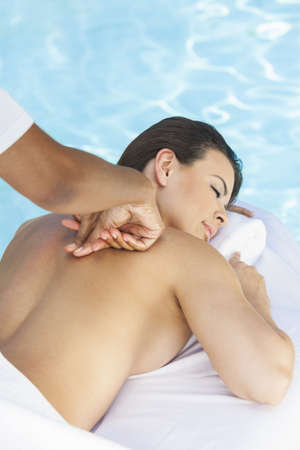 Portrait of a beautiful young Latina Hispanic woman eyes closed laying down, relaxing and having a massage by a swimming pool at a health spa photo