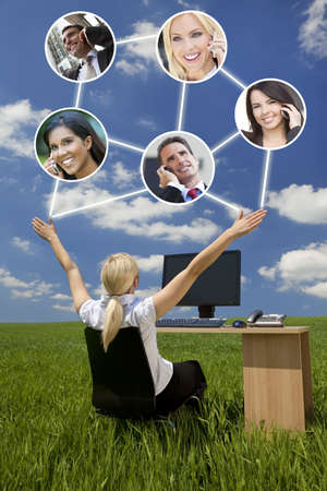 wireless network: Business or social network connections concept photograph of woman businesswoman sitting at a desk using a computer in a green field raising her arms into a bright blue sky with fluffy white clouds