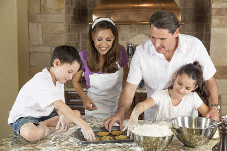 cozimento: Uma fam�lia de sorriso atrativa da m�e, pai e dois filhos assar e comer biscoitos de chocolate frescos em uma cozinha em casa