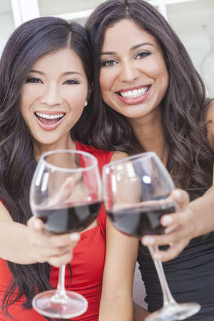 Two beautiful young women friends, Asian Chinese and Hispanic having fun drinking red wine together