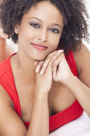 A beautiful mixed race African American girl or young woman laying down wearing a red dress photo