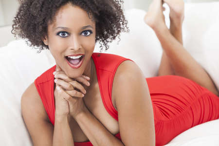settee: A beautiful mixed race African American girl or young woman laying down wearing a red dress looking happy and surprised