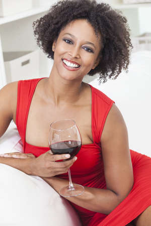 A beautiful happy mixed race African American girl or young woman wearing a red dress and drinking red wine at home